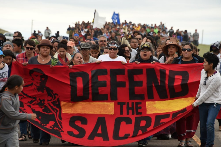 Banner reads: Defend the Sacred - picture of a protest against the pipeline